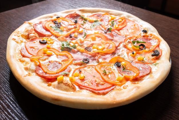 Goedkope pizza, met tomaten, paprika's, ham en olijven. voor elk doel.