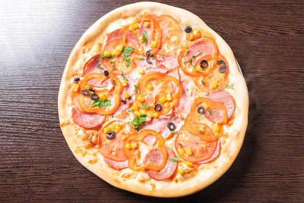 Goedkope pizza, met tomaten, paprika's, ham en olijven. voor welk doel dan ook.