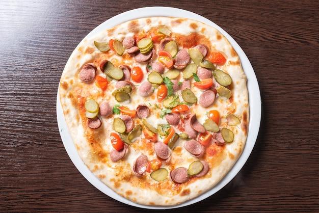 Goedkope pizza met worstjes, komkommers, cherrytomaatjes en kruiden. voor welk doel dan ook.