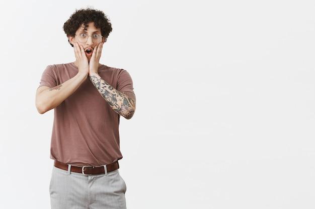 Goh, je maakt een grapje. portret van verrast sprakeloze knappe jonge krullende man in glazen met schattige snor en tatoeages kaak laten vallen, hijgend van verbazing aanraken van gezicht