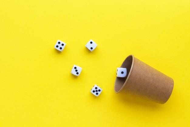 Gokken dobbelstenen en kartonnen beker op gele achtergrond. speelkubus met getallen. items voor bordspellen. plat lag, bovenaanzicht met kopie ruimte.