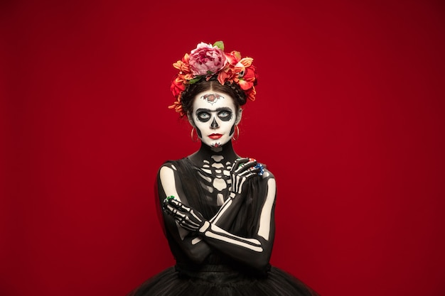 Gokken. jong meisje zoals santa muerte saint dood of suikerschedel met lichte make-up. portret geïsoleerd op rode studio achtergrond met copyspace. het vieren van halloween of dag van de doden.