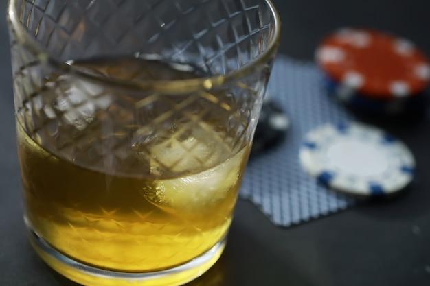 Gokken kaartspellen voor geld. texas hold'em poker. kaarten in de hand, chips spelen, kaartspel alcohol in een glas.