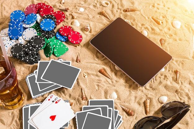 Gokken op vakantieconcept wit zand met schelpen gekleurde pokerfiches en kaarten bovenaanzicht