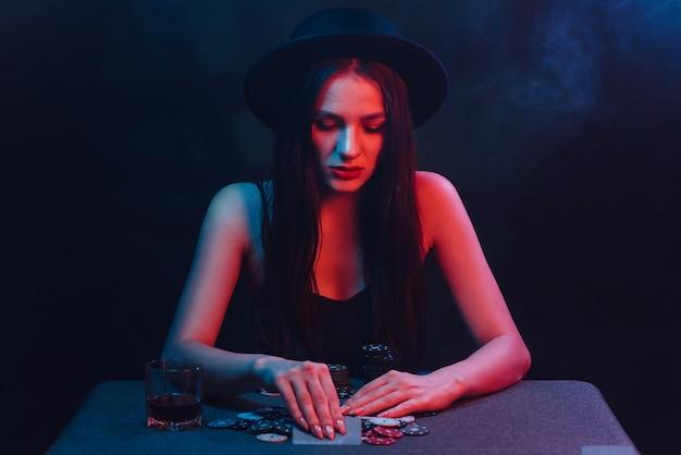 Gokkend meisje in een hoed en jurk speelt poker aan een tafel met kaarten, chips en een weddenschap in een casino