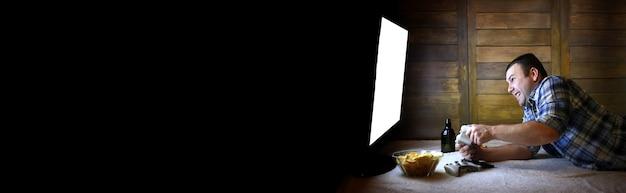 Gokkende man die op een console op de joystick speelt voor het grote tv-scherm en de lange zwarte banner voor tekst