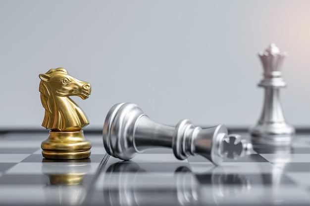 Gold chess knight-figuur onderscheidt zich van de menigte van de vijand tijdens de schaakbordcompetitie.
