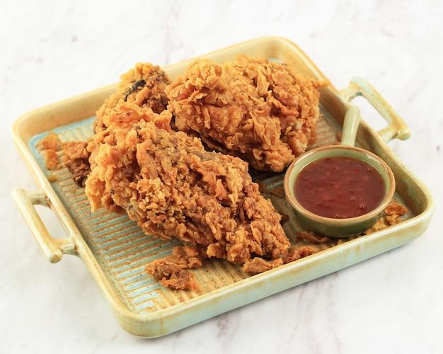 Golden crispy fried chicken breast en chicken wings, geserveerd op een rustieke vierkante plaat met chilisaus, geïsoleerd op een witte achtergrond met kopie ruimte voor tekst