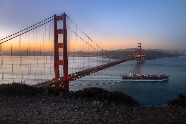 Golden gate bridge en vrachtschip in de mooie ochtend