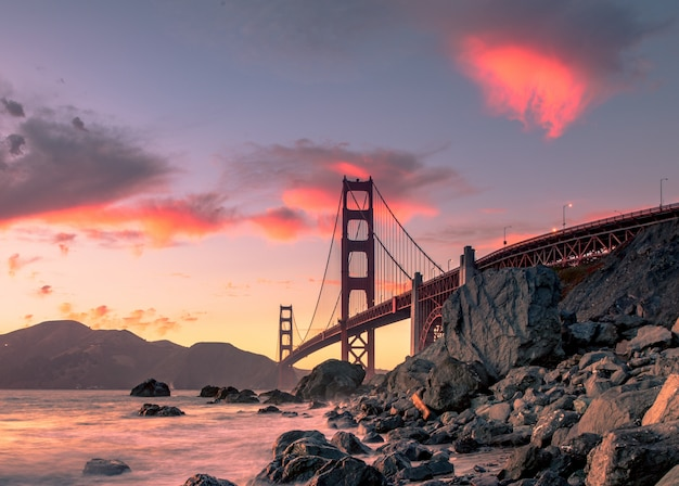 Golden gate bridge op watermassa dichtbij rotsvormingen tijdens zonsondergang in san francisco, californië