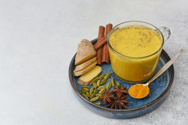 Golden milk, gemaakt met kurkuma en andere kruiden. glazen beker met gouden melk en ingrediënten op lichte achtergrond met kopie ruimte.