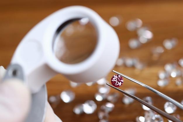 Goldsith in witte handschoenen houdt een pincet met roze diamant vast