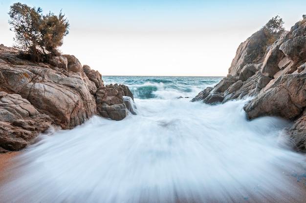 Golf die tegen de rotsen op het strand breekt