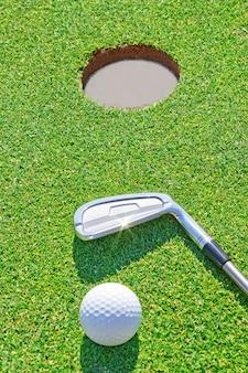 Golf putterbal dichtbij het gat in het verticale formaat. tegen de achtergrond van gras.