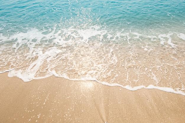 Golf van blauwe oceaan op zandstrand. textuur achtergrond.