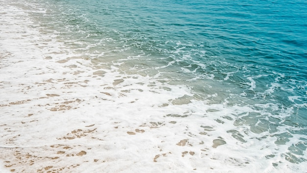 Golf van blauwe oceaan op zandstrand.