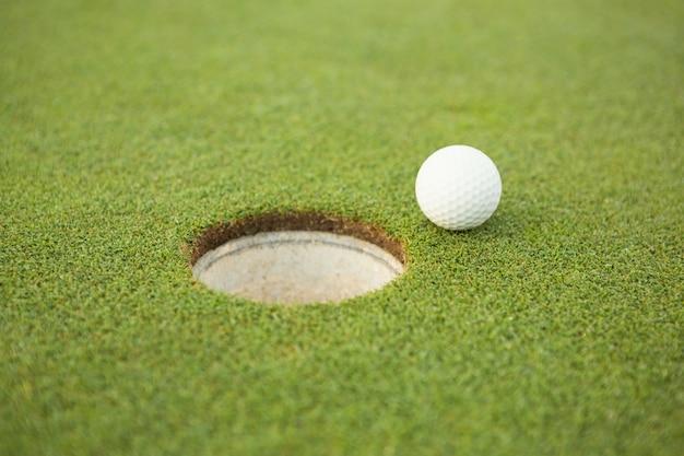 Golfbal aan de rand van het gat