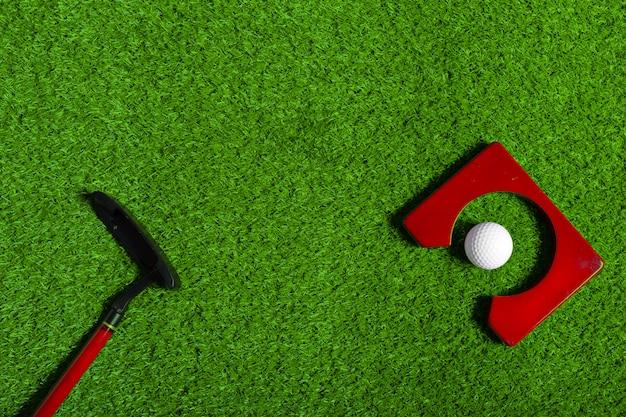 Golfbal en golfclub op gras