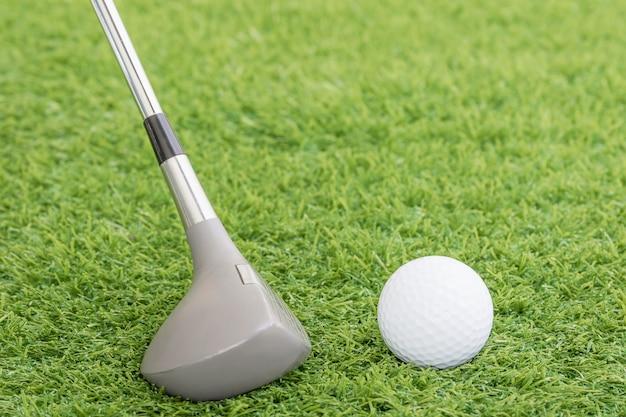 Golfbal en golfclub op groen gras