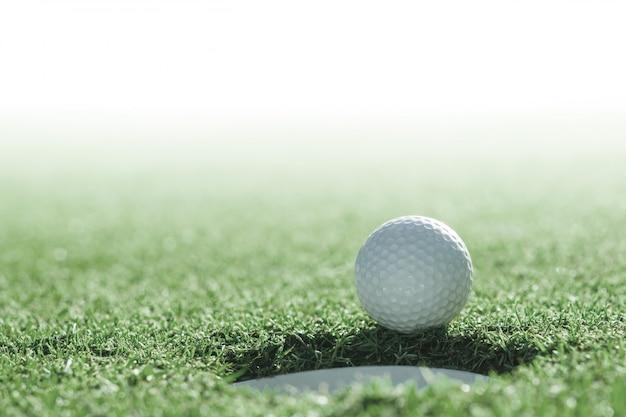 Golfbal en golfgat op groen gras met exemplaarruimte