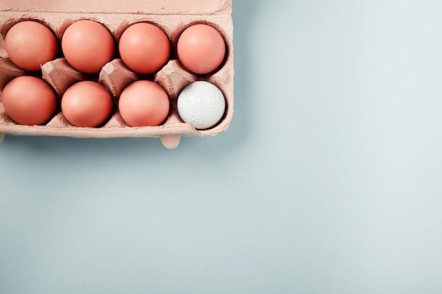 Golfbal in een doos met eieren, flatlay op blauwe achtergrond met veel kopie ruimte ... concept van keuze, conformisme, eenheid, exclusiviteit, moeilijke keuze, enz