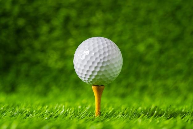 Golfbal met groene grasachtergrond, op t-stukclose-up.