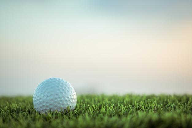 Golfbal op gras op hemelachtergrond
