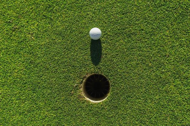 Golfbal op groen gras met gat en zonlicht