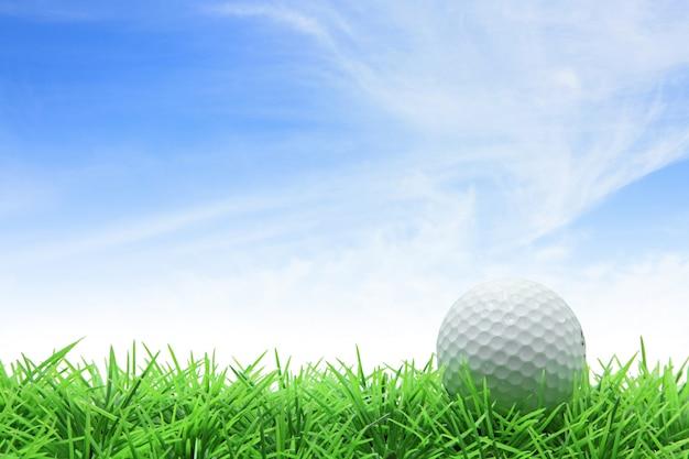 Golfbal op groen gras tegen blauwe hemel