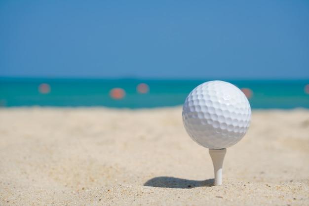 Golfbal op strandzand onder blauwe hemelachtergrond