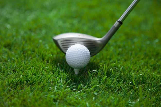 Golfbal op tee en club op golfbaan