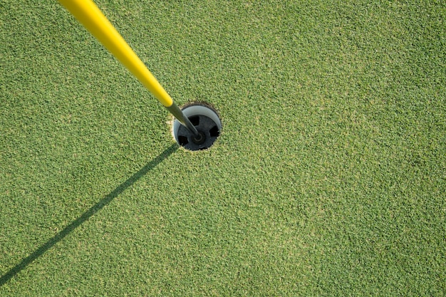 Golfbeker met gele paal op groen veld