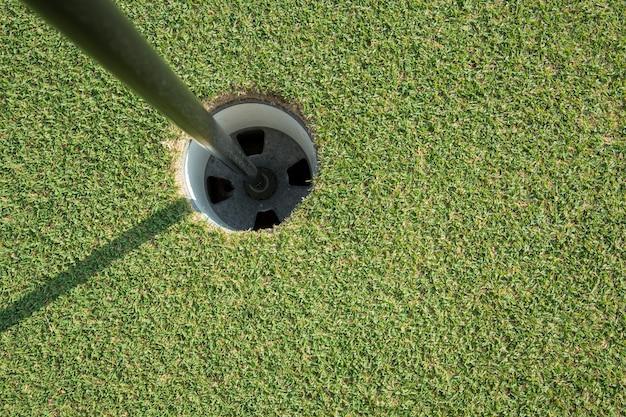 Golfbeker met paal op groen veld