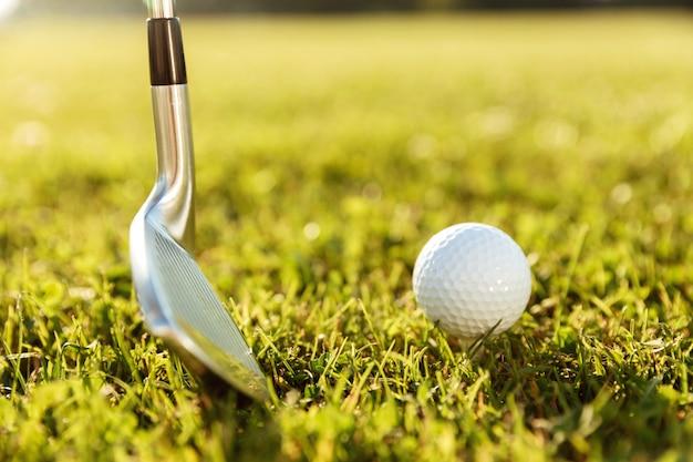 Golfclub en een bal in groen gras