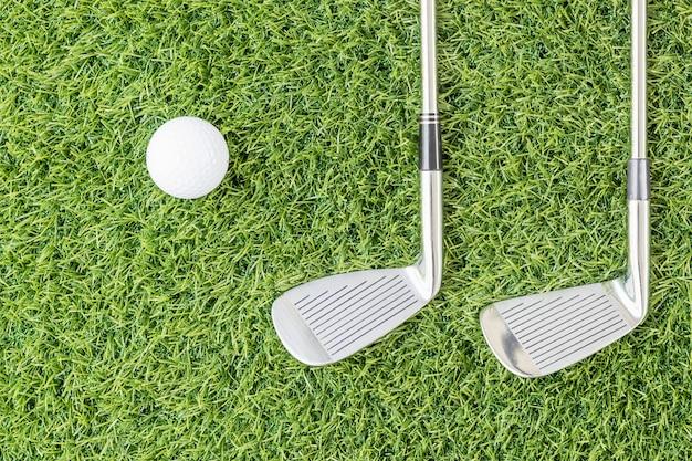 Golfclub en golfbal op groen gras
