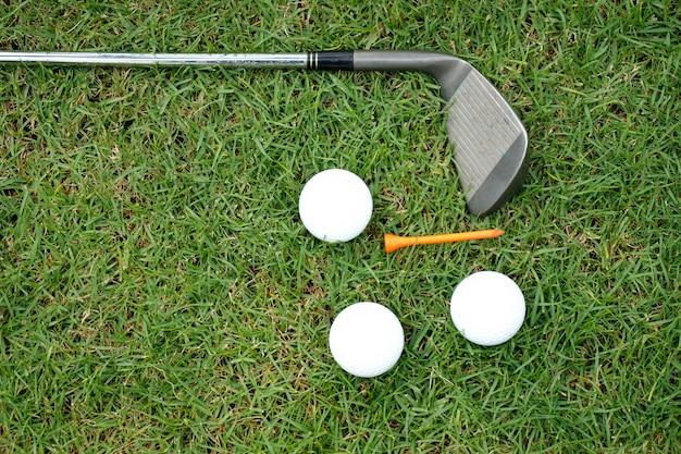 Golfclub en golfballen op groen gras