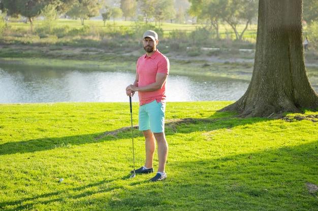 Golfclubman staat op een warme avond op het groene gras van het gazon op een golfveld