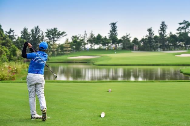 Golfers slaan bij zonsopgang een uitgestrekte golfbaan vanaf de fairway