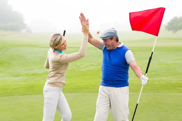 Golfing paar hoge fiving op de golfbaan op een mistige dag op de golfbaan