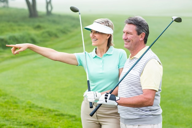 Golfpaar glimlachend en houden van clubs op een mistige dag op de golfbaan
