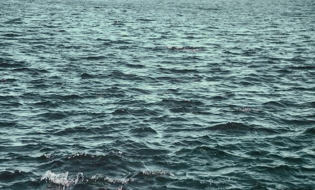 Golfpatroon oppervlakte vers of zee reservoir. wallpaper achtergrond van kabbelende riviergolven op wateroppervlakte zee of oceaangolven. achtergronden natuur wallpapers concept. foto rimpelt meer. ruimte kopiëren