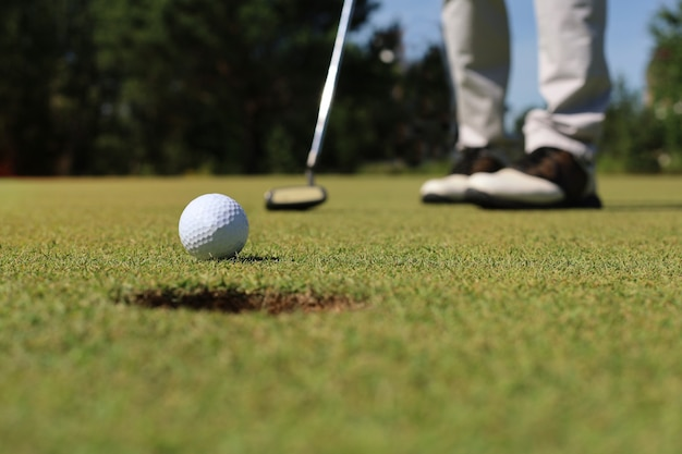 Golfspeler bij de putting green die bal in een gat slaat.