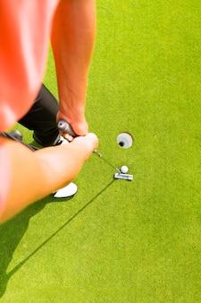 Golfspeler die bal in gat zet