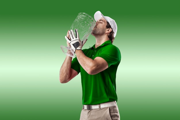 Golfspeler in een groen shirt vieren met een glazen trofee in zijn handen, op een groene achtergrond.