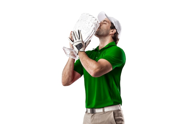 Golfspeler in een groen shirt vieren met een glazen trofee in zijn handen, op een witte achtergrond.