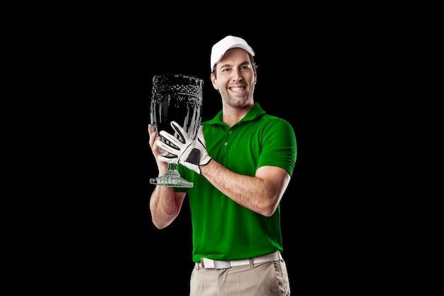 Golfspeler in een groen shirt vieren met een glazen trofee in zijn handen, op een zwarte achtergrond.