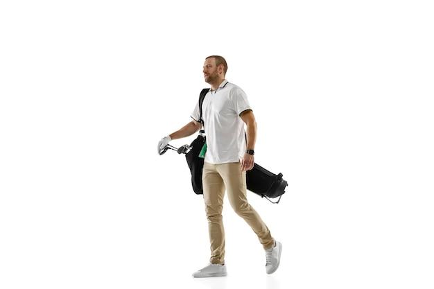 Golfspeler in een wit overhemd die een schommel nemen die op witte muur met copyspace wordt geïsoleerd. professionele speler die oefent met heldere emoties en gezichtsuitdrukkingen. sport concept.