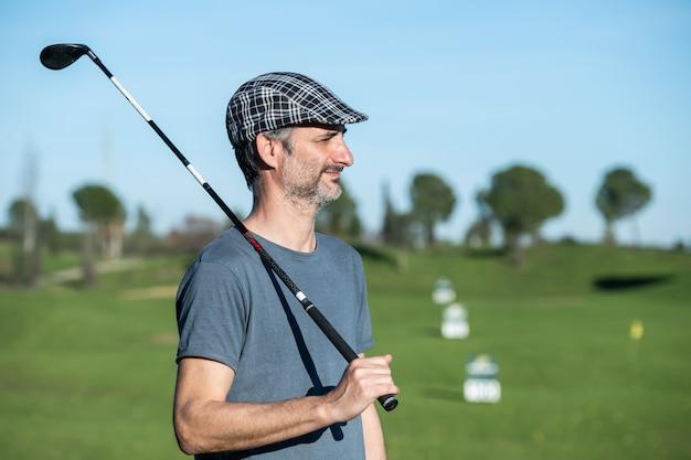 Golfspeler met pet en club over zijn schouder op een rijbaan