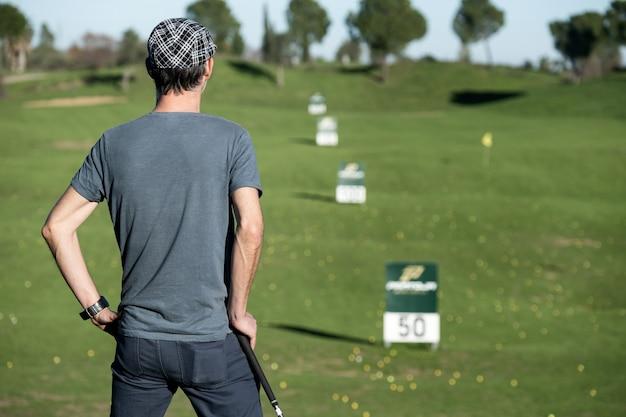 Golfspeler op zijn rug die op een golfclub leunt die de horizon bekijkt