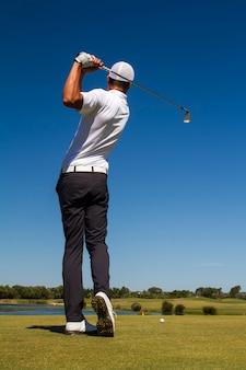 Golfspeler raakt een golfbal in een prachtige golfbaan.